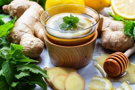 Zázvorový čaj v pohári s citrónom, mätou a medom.
