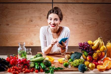 Usmiata žena drží zdravú diétu a má pred sebou na stole ovocie, zeleninu a vodu